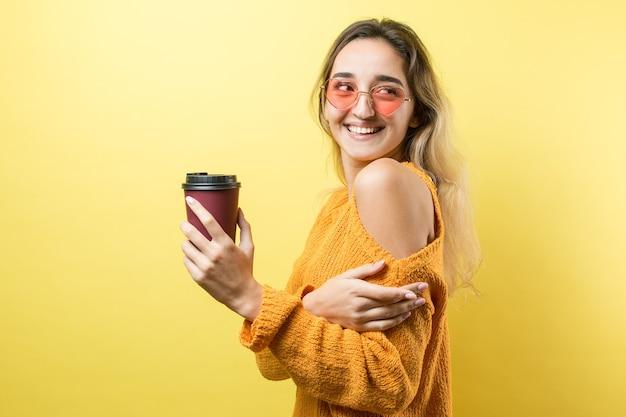 Glamour-frau in gläsern in einem orangefarbenen pullover mit einem getränk kaffee auf gelbem hintergrund
