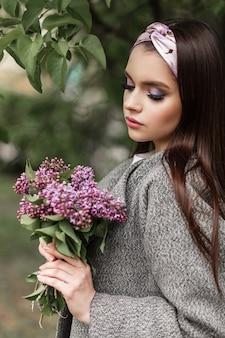 Glamour-frau mit farb-make-up mit modischem bandana in grauem, stilvollem mantel mit blumenstrauß-flieder genießen den frühling auf grünem hintergrundlaub im park. wunderschönes mädchenmodell des frischen porträts mit purpurroten blumen.