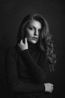Glamour-frau mit lockigen langen haaren trägt einen schwarzen rollkragenpullover. studioaufnahme. schwarze und weiße farben