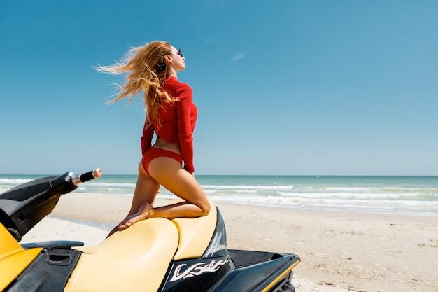 Glamour-girl im roten bikini auf dem wasserscooter. perfektes körperbikinimodell langes blondes haar. wassersport, sommerlebensstil. blauer ozean im hintergrund.