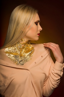 Glamour-junges model mit hellem make-up in roter farbe und goldfolie am hals