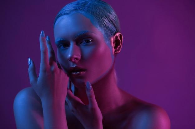 Glamour junges modell posiert wie pro für kamera auf lila.
