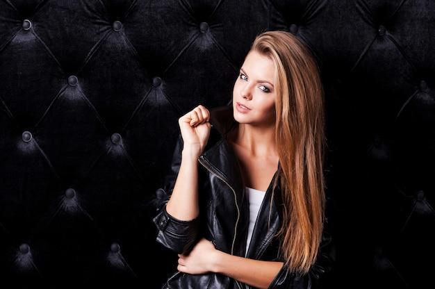 Glamour-mode-modell. schöne junge frau mit make-up und frisur posiert vor schwarzem hintergrund