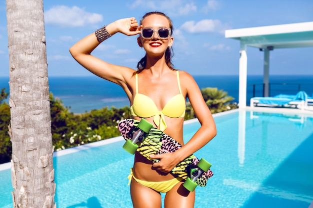 Glamour-mode-porträt der atemberaubenden sexy frau mit perfektem körper, der helles skateboard hält und nahe luxus-vila mit pool und blick auf die exotische ozeaninsel aufwirft.