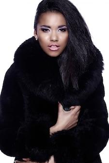 Glamour nahaufnahme porträt des schönen sexy schwarzen jungen frau modell mit hellem make-up mit perfekt sauber im pelzmantel
