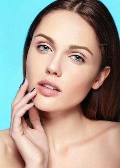 Glamour-nahaufnahme-schönheitsporträt des schönen sinnlichen kaukasischen jungen frauenmodells mit nacktem make-up, das ihre vollkommen saubere haut lokalisiert auf blauem hintergrund berührt