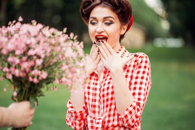 Glamour pinup girl nimmt geschenk einen blumenstrauß, retro amerikanische mode. attraktive frau im pin-up-stil