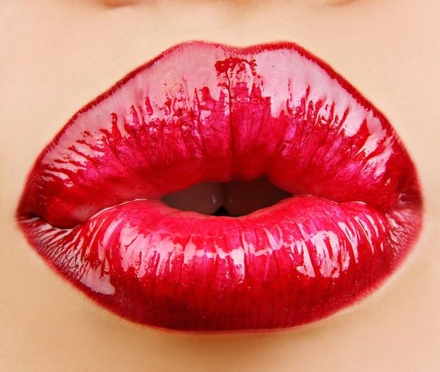 Glamour red glänzende lippen mit kussgeste.