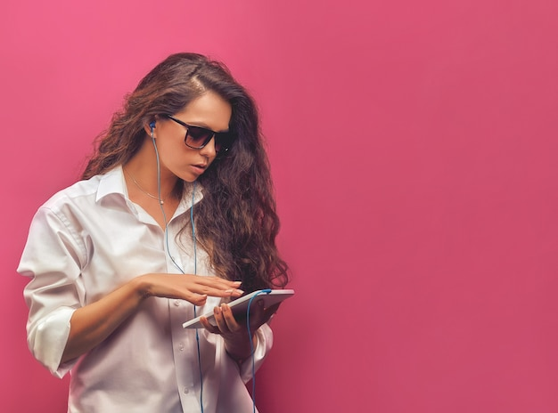 Glamour schöne junge frau in einem weißen hemd in gläsern mit kopfhörern, eine weiße tablette in den händen auf einer rosa hellen wand haltend.