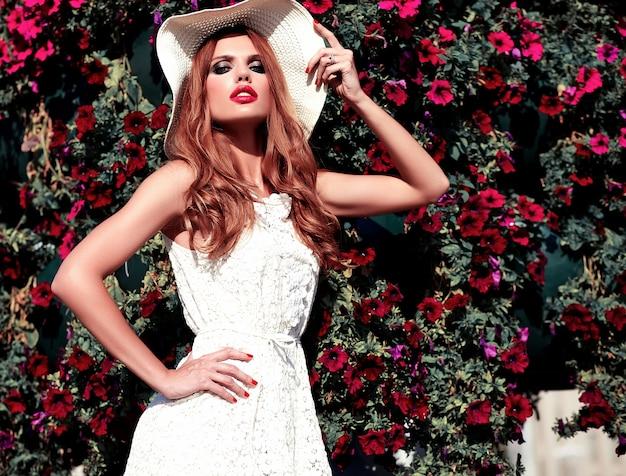 Glamour-schönheitsporträt des schönen sinnlichen kaukasischen jungen frauenmodells mit abendmake-up im weißen sommerkleid, das auf dem straßenhintergrund nahe blumenhintergrund aufwirft