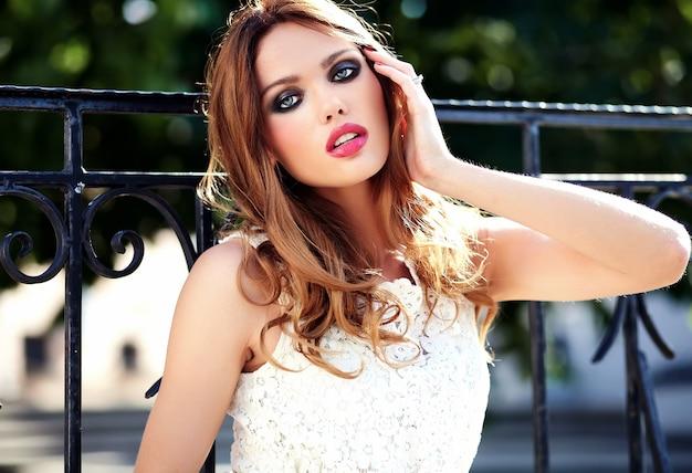 Glamour-schönheitsporträt des schönen sinnlichen kaukasischen jungen frauenmodells mit abendmake-up im weißen sommerkleid, das auf der straße aufwirft