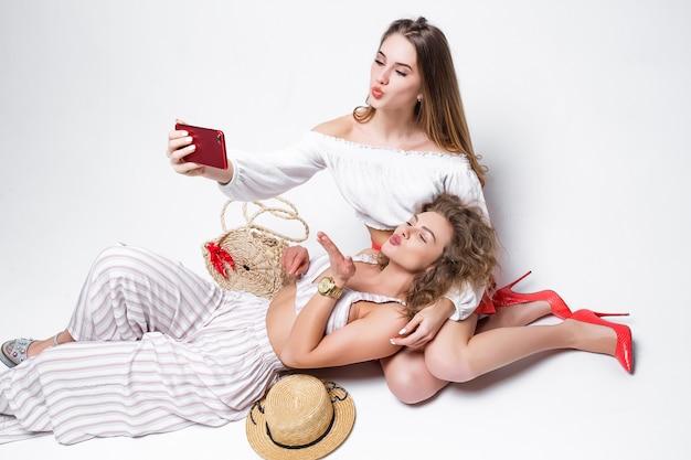 Glamour-schwestern machen selfies und geben küsse, während sie auf dem boden liegen.