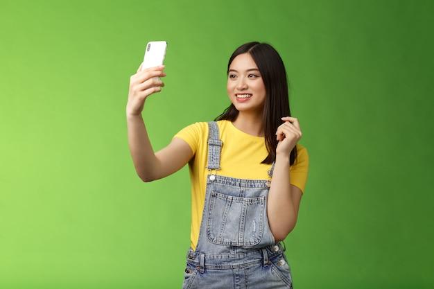 Glamour zarte teenager asiatische frau unter selfie checkt haarschnitt look smartphone frontkamera phot...