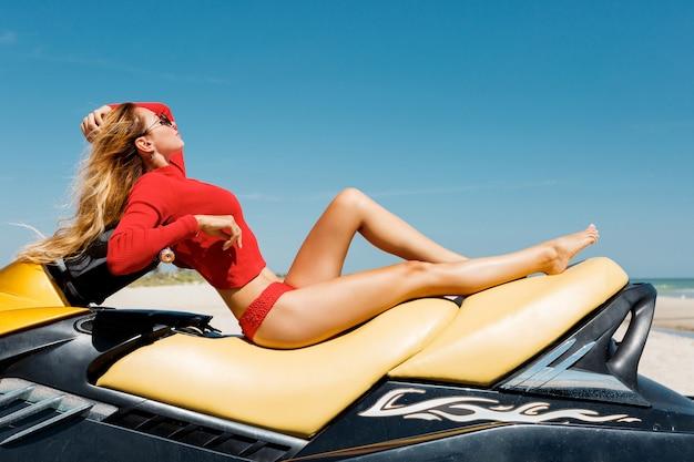 Glamourblonde frau im stilvollen roten sommeroutfit posiert auf wasserscooter am tropischen strand. sommerstimmung, wassersport, urlaubszeit.