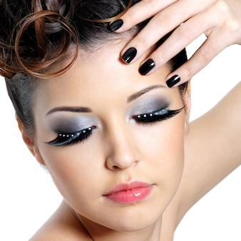 Glamourfrau mit mode-augen-make-up und schwarzen nägeln nahe dem gesicht