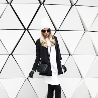 Glamouröse blondine steht an der wand. urban fashion schwarz-weiß-stil