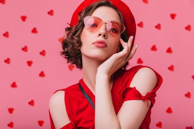 Glamouröse braunhaarige frau mit blasser haut posiert. nette ernste dame in der weinlese baskenmütze suchen.