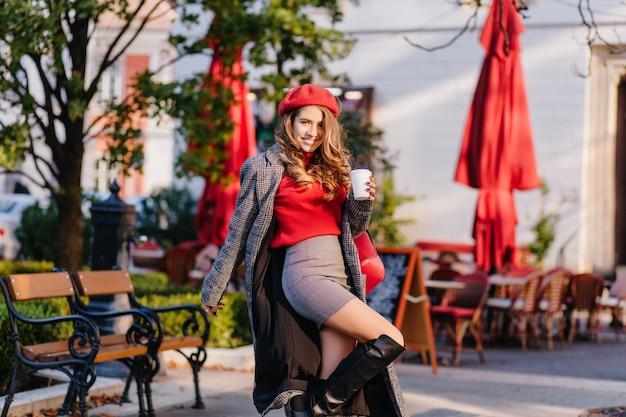 Glamouröse dame in eleganten kniehohen stiefeln, die im park mit tasse kaffee tanzen