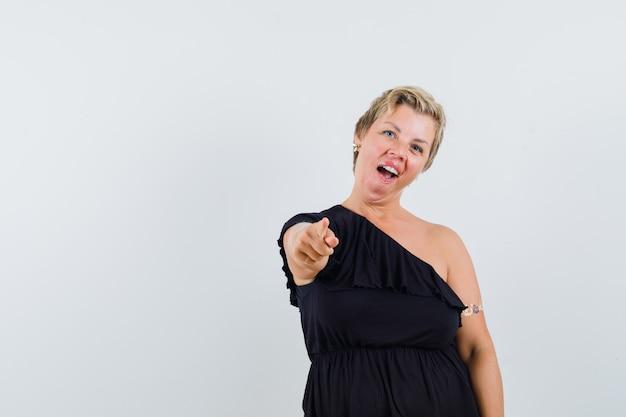 Glamouröse frau, die auf kamera in schwarzer bluse zeigt und lustig schaut