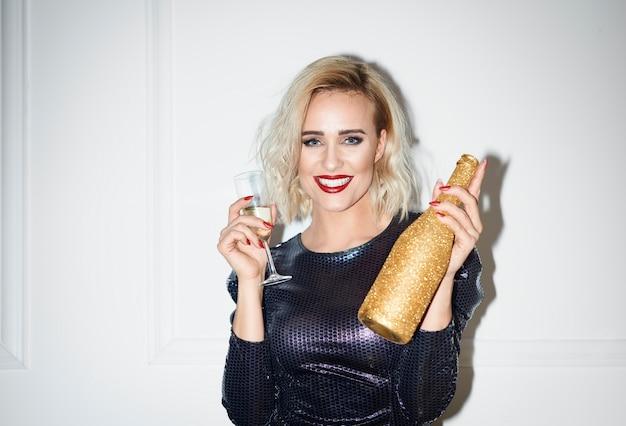 Glamouröse frau, die flasche champagner hält