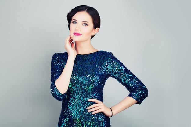 Glamouröse frau in modischem glitzerkleid posiert