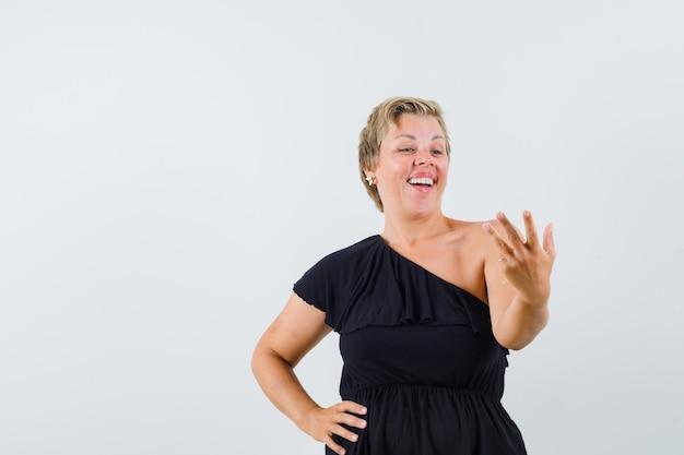 Glamouröse frau posiert wie telefon in schwarzer bluse halten und optimistisch aussehen