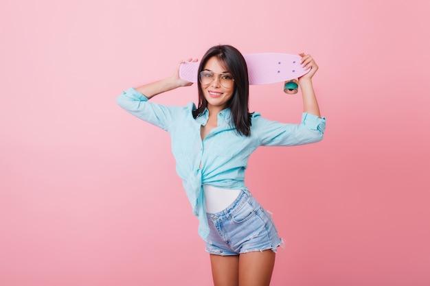 Glamouröse hispanische junge dame in der trendigen kleidung, die in der selbstbewussten haltung steht und skateboard hält. tolles schwarzhaariges mädchen in jeansshorts und trendiger sonnenbrille posiert im blauen raum.