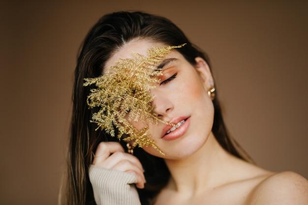 Glamouröse junge frau, die mit geschlossenen augen auf brauner wand aufwirft. gut gelaunte angenehme dame, die pflanze hält.