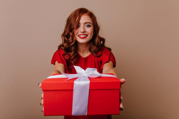 Glamouröse junge frau, die weihnachtsgeschenk hält. wunderbares lockiges weibliches modell, das sich auf neujahrsparty vorbereitet.