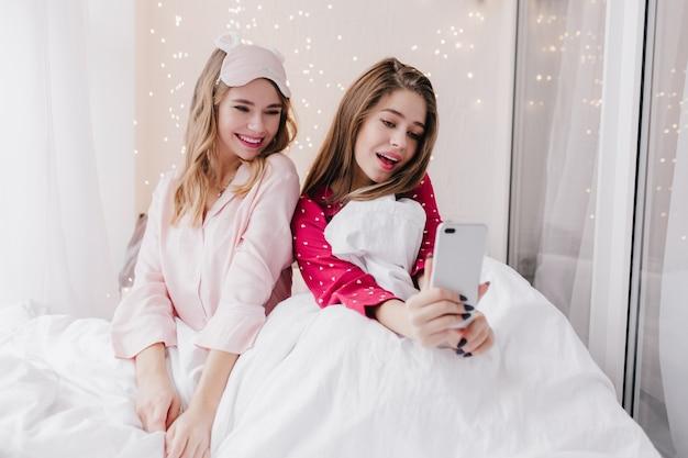 Glamouröse junge frau im roten schlafanzug, der selfie im bett macht. dunkelhaariges mädchen, das mit der besten freundin im schlafzimmer sitzt und sich selbst fotografiert.