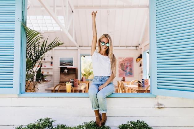 Glamouröse junge frau in den blauen jeans, die auf fensterbank sitzen.