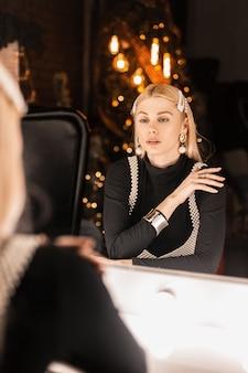 Glamouröse junge frau in einem schwarzen hemd in einem perlenoberteil mit haarspangen sitzt in der nähe eines vintage-spiegels mit hellen lampen im dunklen wohnzimmer