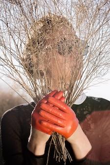 Glamouröse junge frau in orange handschuhen mit einem trockenen blumenstrauß