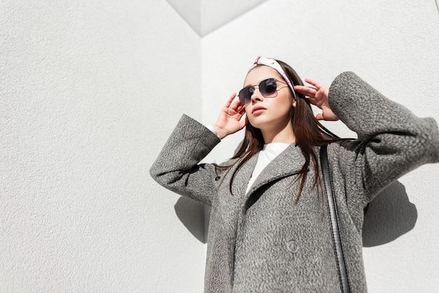 Glamouröse junge frau in stilvoller frühlingskleidung glättet an sonnigen tagen die haare in der nähe der wand. feines mädchen in trendiger kleidung mit sonnenbrille in bandana posiert an einem sonnigen tag auf der straße in der stadt. jugendmode.
