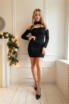 Glamouröse junge frau mit einem sexy geraden körper in einem schwarzen eleganten kleid steht in der nähe einer weißen wand drinnen
