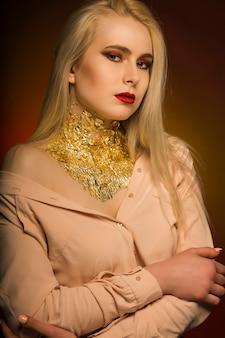 Glamouröse junge frau mit hellem make-up in roter farbe und goldfolie am hals
