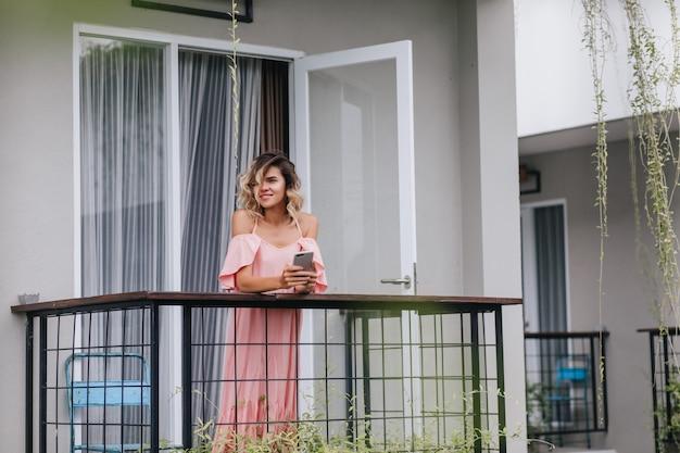 Glamouröse lockige dame, die am balkon mit smartphone steht. charmantes kaukasisches mädchen, das stadt von der terrasse betrachtet.