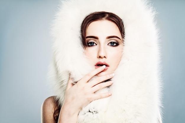 Glamouröse model frau mit weißem fell und make-up