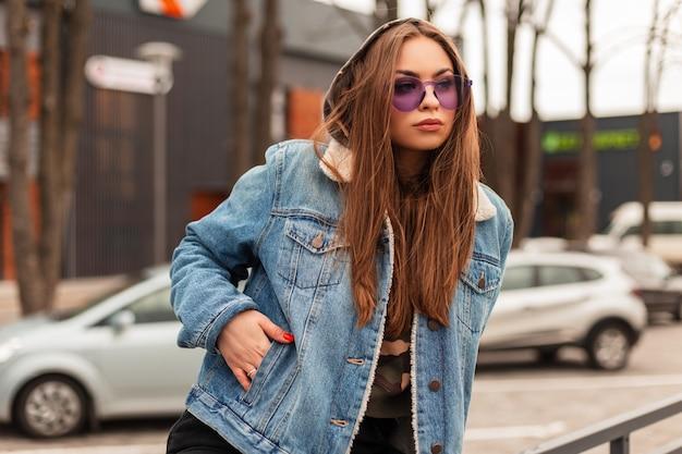 Glamouröse, schöne junge hipster-frau in trendiger lila brille in übergroßer blue jeans-jacke mit langen haaren ruht in der nähe des parkplatzes in der stadt. modernes urbanes mädchenmodell in stilvoller kleidung im freien.