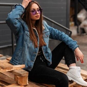 Glamouröse, stilvolle junge hipster-frau in trendiger jeanskleidung in violetter modischer brille in weißen lederstiefeln, die auf holzpaletten in der nähe der wand auf der straße sitzen. amerikanisches mädchen. lässige damenbekleidung.