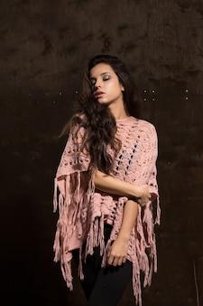 Glamouröses gebräuntes model mit langen, üppigen haaren, die im pullover auf schwarzem hintergrund posieren