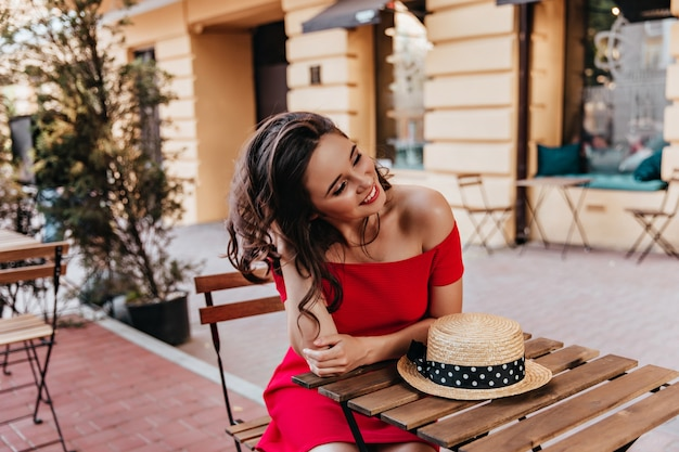 Glamouröses mädchen, das im straßencafé mit lächeln sitzt. attraktive brünette frau im roten kleid, das im straßenrestaurant kühlt.