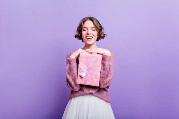 Glamouröses mädchen mit dem lockigen kurzen haar, das mit rosa geschenkbox aufwirft und lacht. attraktives weibliches modell mit weihnachtsgeschenk lokalisiert auf lila wand und lächelnd.