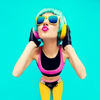 Glamouröses mode-dj-mädchen in hellen kleidern auf blauem hintergrund, das musik hört.