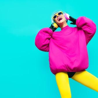 Glamouröses model in hellen kleidern auf blauem hintergrund, das musik hört. alle schattierungen von musik