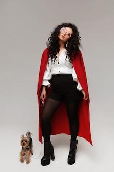 Glamouröses model-mädchen in einem modischen roten mantel und einer trendigen sonnenbrille, die mit süßem yorkshire-terr...
