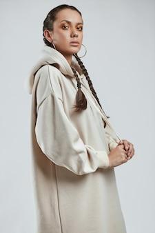 Glamouröses modeporträt des schönen charmanten hispanischen mädchens im langen kapuzenpulli im studio