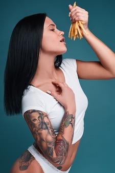 Glamouröses modeporträt des schönen charmanten mädchens mit tätowierung, die eine pommes frites auf einem hellen hintergrund im studio hält