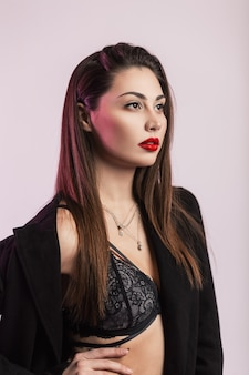 Glamouröses modernes modemodell der jungen frau mit roten lippen mit langen haaren im modischen schwarzen mantel in sexy spitzen-bh, der in der nähe der rosafarbenen wand im studio posiert. schönes brunettemädchen in der eleganten kleidung.