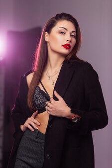Glamouröses porträt junge attraktive frau mit geschwollenen sexy roten lippen mit langen braunen haaren in modischem spitzen-bh im stilvollen schwarzen mantel im studio mit hellem licht. elegantes sinnliches mädchenmode-modell